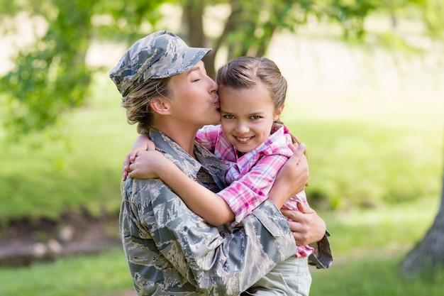 Gelukkige vrouwelijke militair die haar dochter in park kust