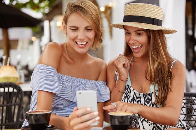 Gelukkige vrouwelijke modellen rusten samen in cafetaria, surfen op sociale netwerken op mobiele telefoon, drinken koffie of cappuccino. vrolijke brunette jonge vrouw geeft aan op mobiele telefoon, deelt foto's met vriend