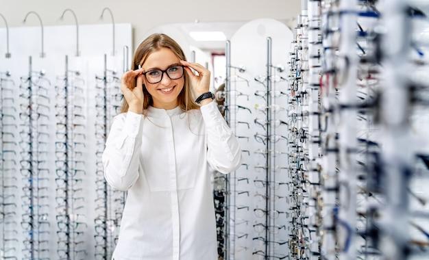 Gelukkige vrouwelijke optometrist met reeks glazen