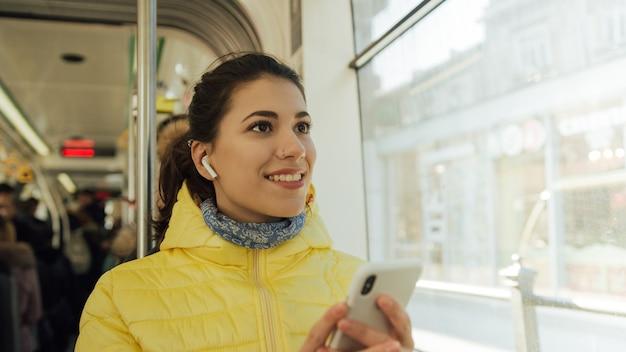Gelukkige vrouwelijke passagier die aan muziek op een smartphone in openbaar vervoer luistert.