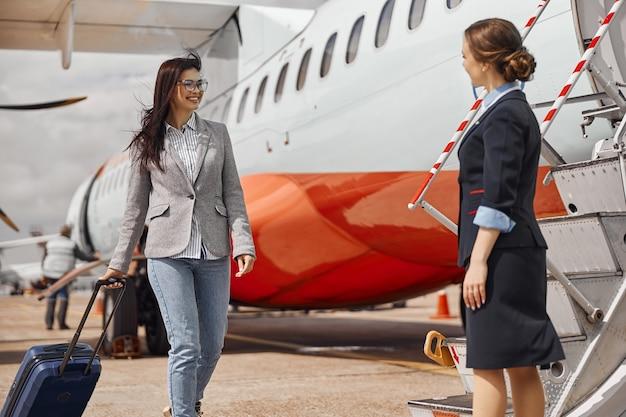 Gelukkige vrouwelijke passagier stapt in een vliegtuig