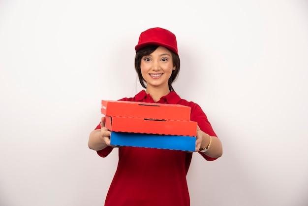 Gelukkige vrouwelijke pizzabezorger die drie kartonnen pizza's geeft