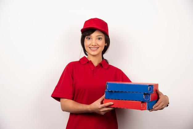 Gelukkige vrouwelijke pizzabezorger die drie kartonnen pizza's vasthoudt