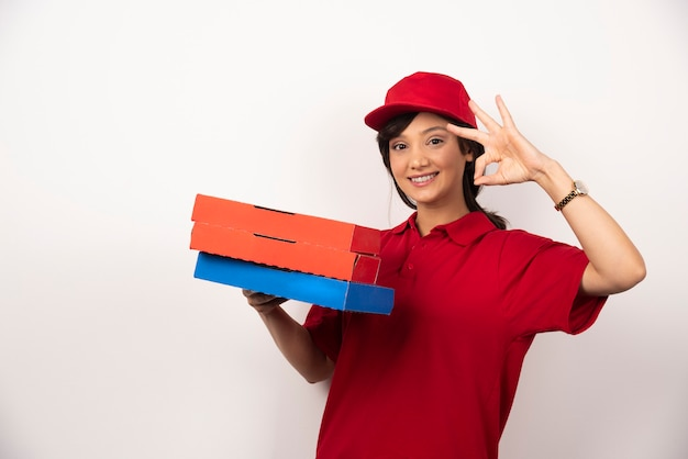 Gelukkige vrouwelijke pizzabezorger die zich met drie kartonnen pizza's bevindt.