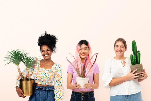 Gelukkige vrouwelijke plantenliefhebbers die kamerplanten in potten houden