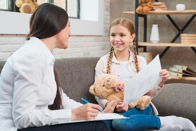 Gelukkige vrouwelijke psycholoog die met een meisje spreekt en nota op papier maakt