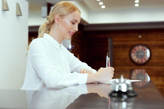 Gelukkige vrouwelijke receptioniste die aan de balie van het hotel staat