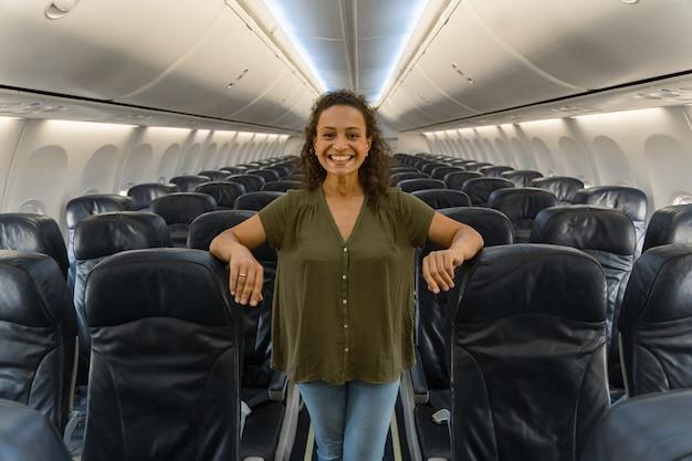 Gelukkige vrouwelijke reiziger die met het vliegtuig gaat reizen