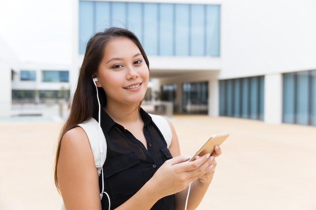 Gelukkige vrouwelijke student die aan muziek op cel luistert