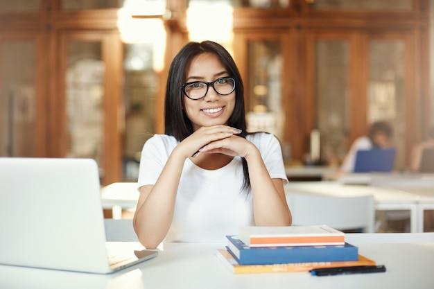 Gelukkige vrouwelijke student die camera bekijkt die in een bibliotheek of open ruimtecampus leert. toekomstige oosterse ingenieur of advocaat.
