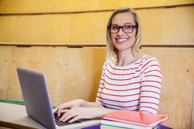 Gelukkige vrouwelijke student die op laptop bij de universiteit typt