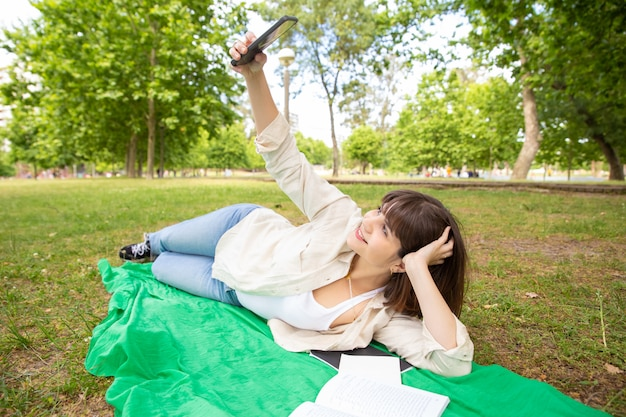 Gelukkige vrouwelijke student die selfie in park nemen