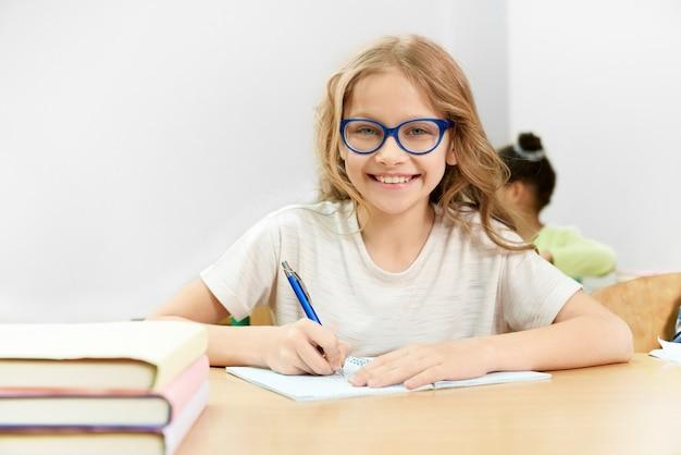 Gelukkige vrouwelijke student die tijdens les op school leert