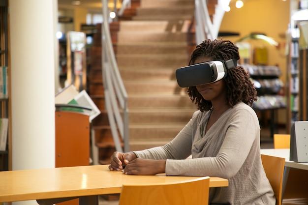Gelukkige vrouwelijke student die van vr-ervaring in bibliotheek geniet