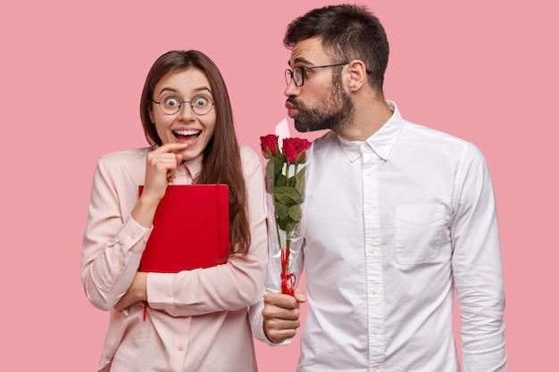 Gelukkige vrouwelijke student in bril, draagt rood leerboek, blij een boeket rozen te ontvangen van mannelijke wonk