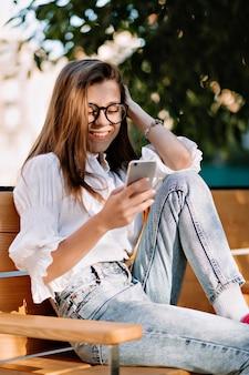 Gelukkige vrouwelijke student met lang lichtbruin haar in bril