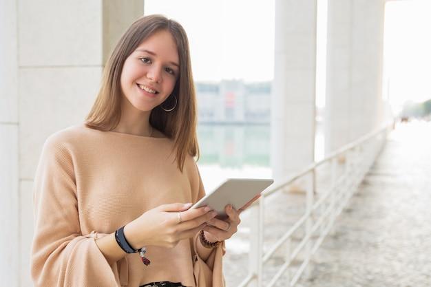 Gelukkige vrouwelijke tiener die op tabletcomputer in openlucht doorbladeren