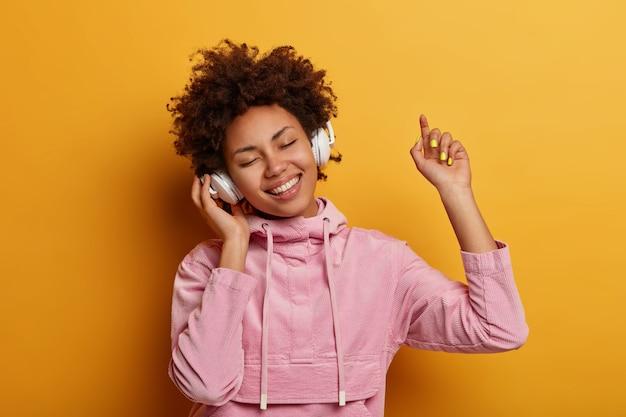 Gelukkige vrouwelijke tiener geniet van aangename muziek
