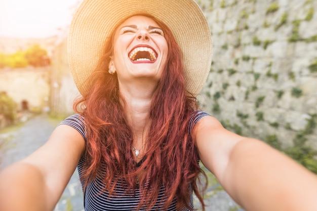 Gelukkige vrouwelijke toerist naast muur