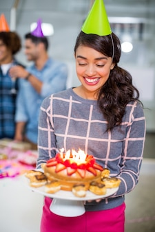 Gelukkige vrouwelijke uitvoerende die partijhoed draagt en verjaardagstaart houdt