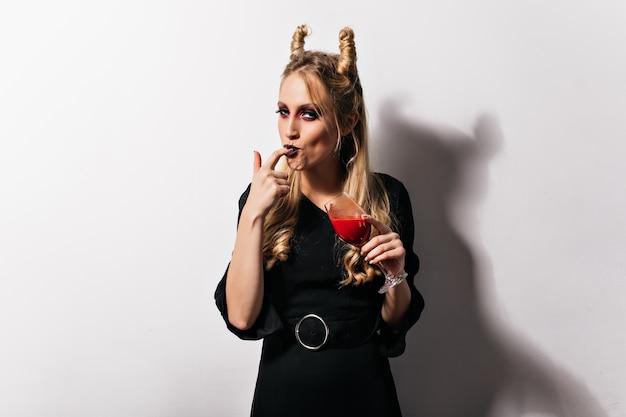 Gelukkige vrouwelijke vampier die bloed proeft. charmante jonge heks met donkere make-up drinkdrank.
