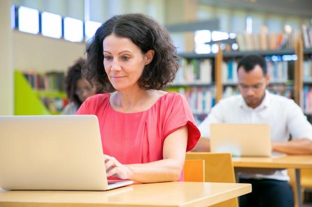 Gelukkige vrouwelijke volwassen student die online test overgaat