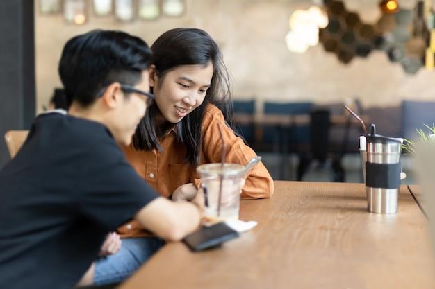 Gelukkige vrouwelijke vriend die celtelefoon in koffie bekijkt.