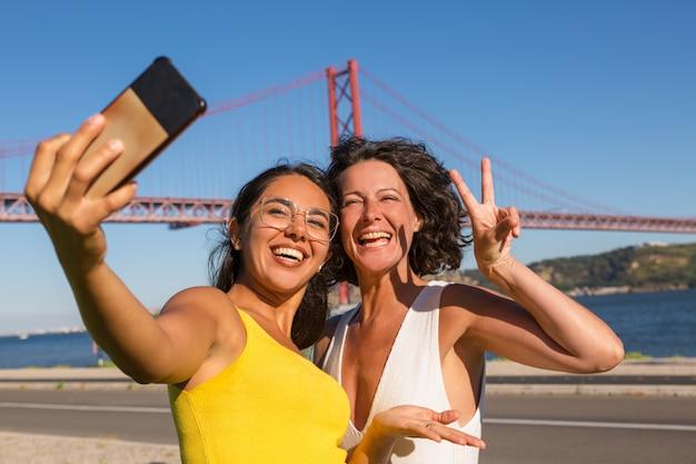 Gelukkige vrouwelijke vrienden die voor selfie stellen
