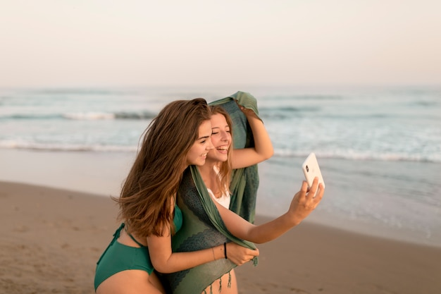 Gelukkige vrouwelijke vrienden die zelfportret nemen bij strand