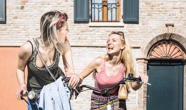 Gelukkige vrouwelijke vriendenpaar die pret berijdende fiets in stads oude stad hebben