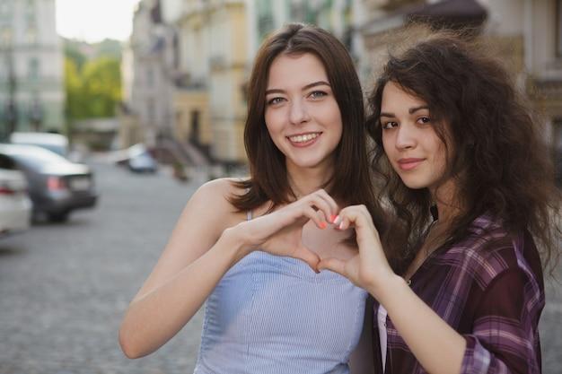 Gelukkige vrouwen die aan de camera glimlachen, die een hart met hun handen tonen, exemplaarruimte