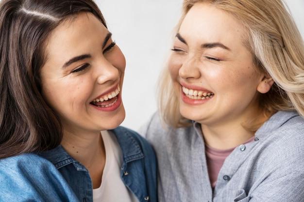 Gelukkige vrouwen die en elkaar glimlachen omhelzen