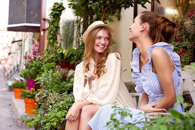 Gelukkige vrouwen die en in een park met een groene achtergrond spreken lachen