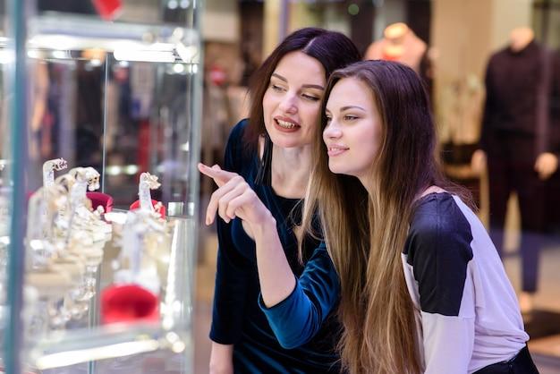 Gelukkige vrouwen die in de mall winkelen voor sieraden