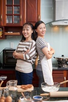 Gelukkige vrouwen die in keuken stellen