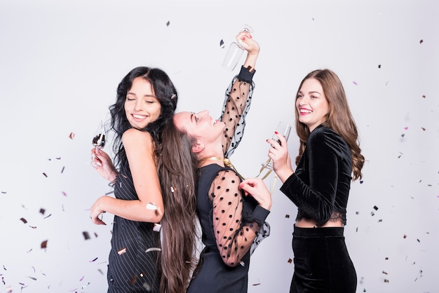 Gelukkige vrouwen die met glazen champagne dansen