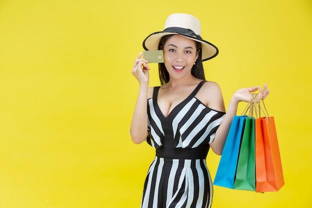 Gelukkige vrouwen die met het winkelen zakken en creditcards winkelen