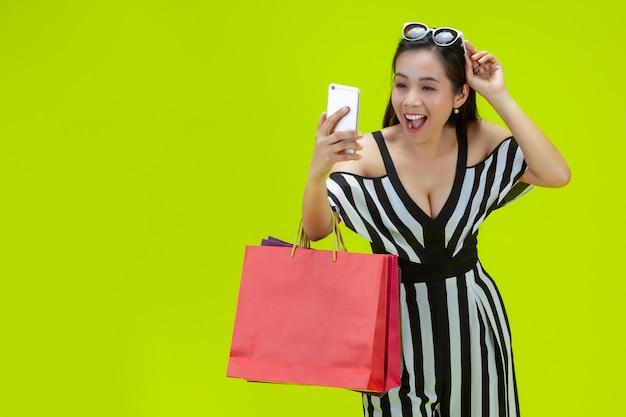 Gelukkige vrouwen die online met een slimme telefoon kopen