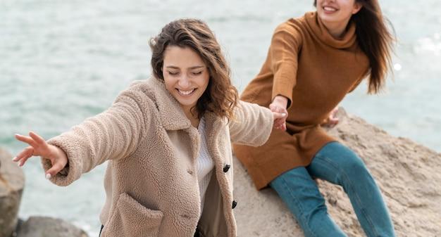 Gelukkige vrouwen die samen dicht omhoog stellen