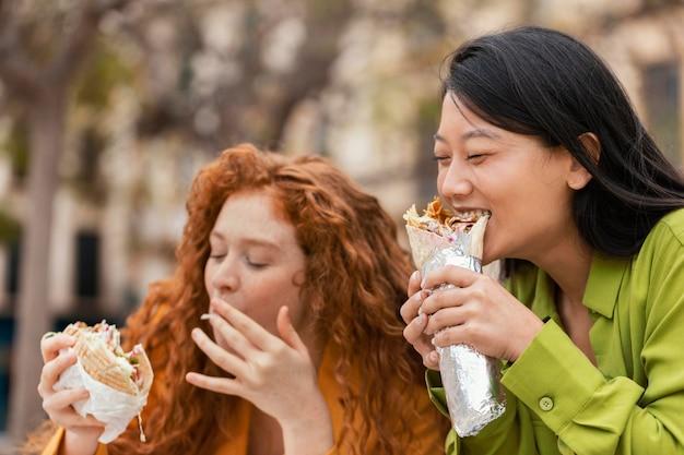 Gelukkige vrouwen die samen straatvoedsel eten