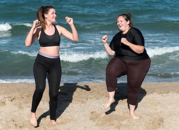 Gelukkige vrouwen die samen volledig schot trainen