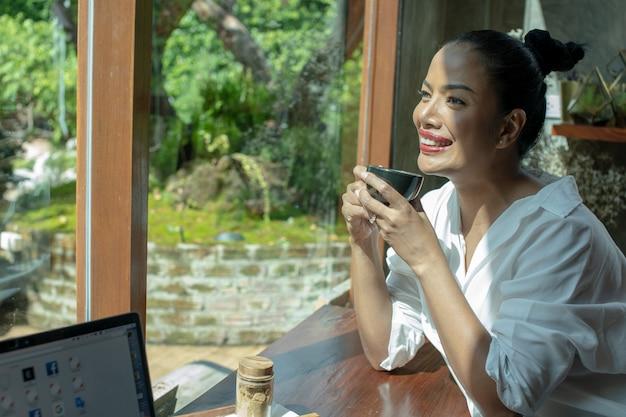 Gelukkige vrouwen die van koffie in een koffie genieten.