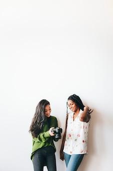 Gelukkige vrouwen met een digitale camera aan het praten