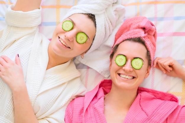 Gelukkige vrouwen met handdoeken op het hoofd en plakjes komkommer op de ogen