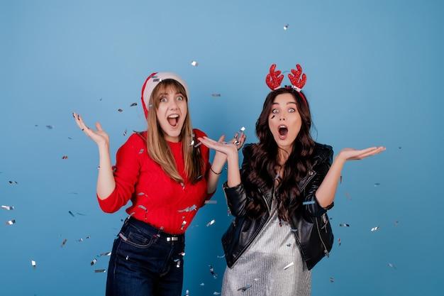 Gelukkige vrouwen met zilveren confettien in de lucht die kerstmishoed dragen die over blauw wordt geïsoleerd