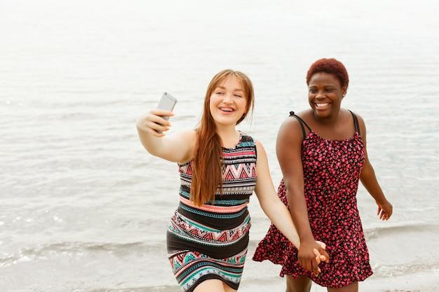Gelukkige vrouwen op het strand hand in hand en selfie te nemen