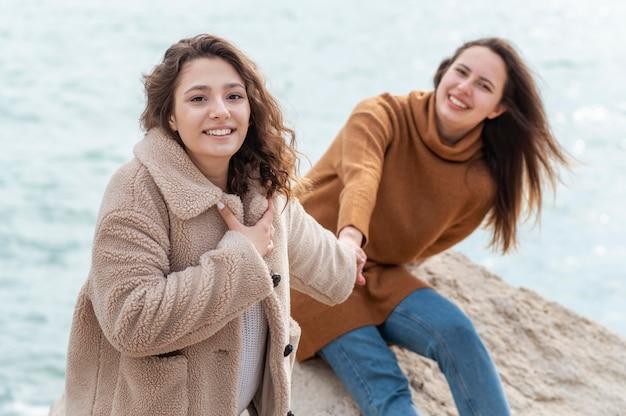 Gelukkige vrouwen samen poseren aan zee