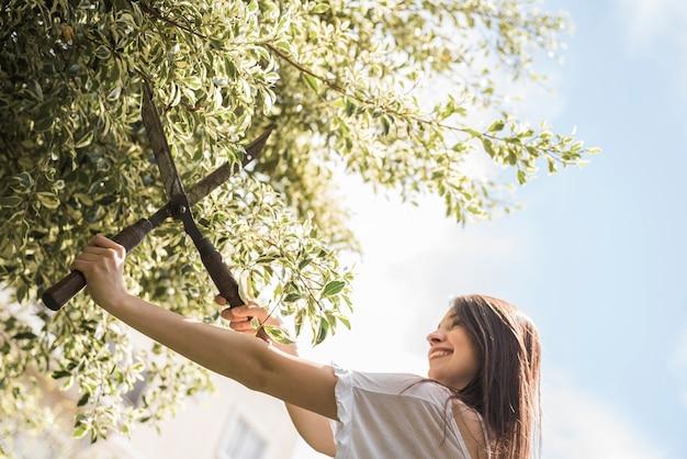 Gelukkige vrouwen scherpe bladeren met het tuinieren schaar