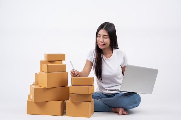 Gelukkige vrouwen van het bestellen van producten van klanten, ondernemers die thuis werken op een witte achtergrond