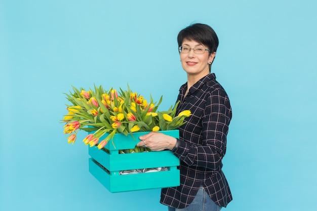 Gelukkige vrouwenbloemist die van middelbare leeftijd glazen met doos tulpen op blauwe achtergrond dragen